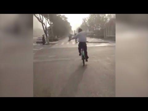 chinese man practices tai chi while riding bike