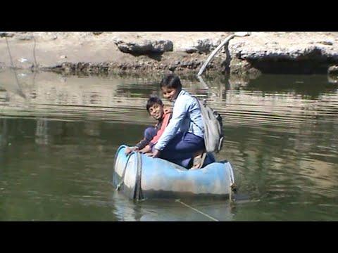 شاهد تلاميذ قرية فقيرة يعبرون النهر بقارب مصنوع من الطبول